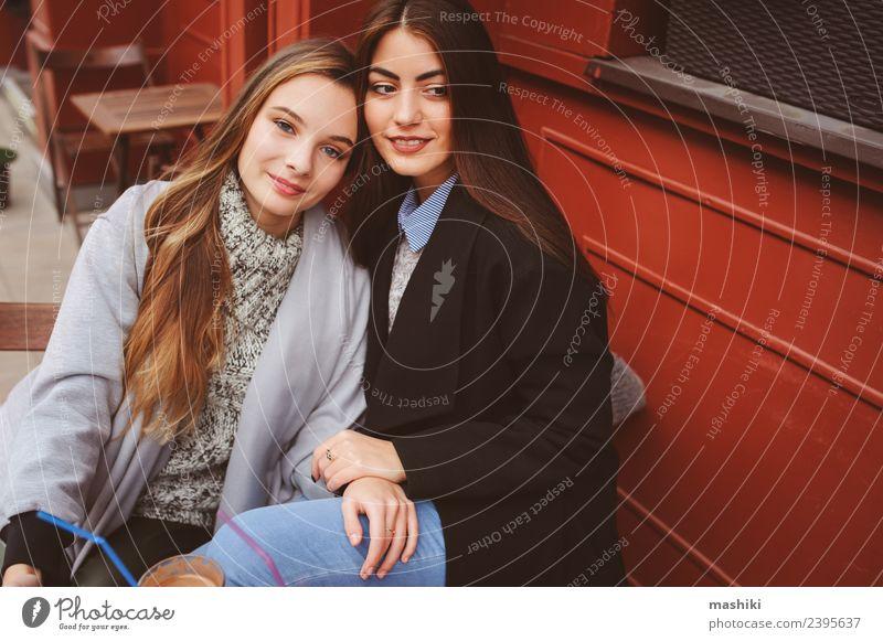 zwei glückliche Freundinnen im Gespräch Kaffee Lifestyle sprechen feminin Frau Erwachsene Freundschaft Herbst Wetter Straße Pullover Mantel Lächeln lachen