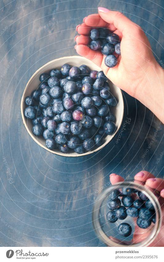 Frau, die frische Heidelbeeren aus einem Glas in eine kleine Schüssel legt. Lebensmittel Frucht Ernährung Bioprodukte Vegetarische Ernährung Diät