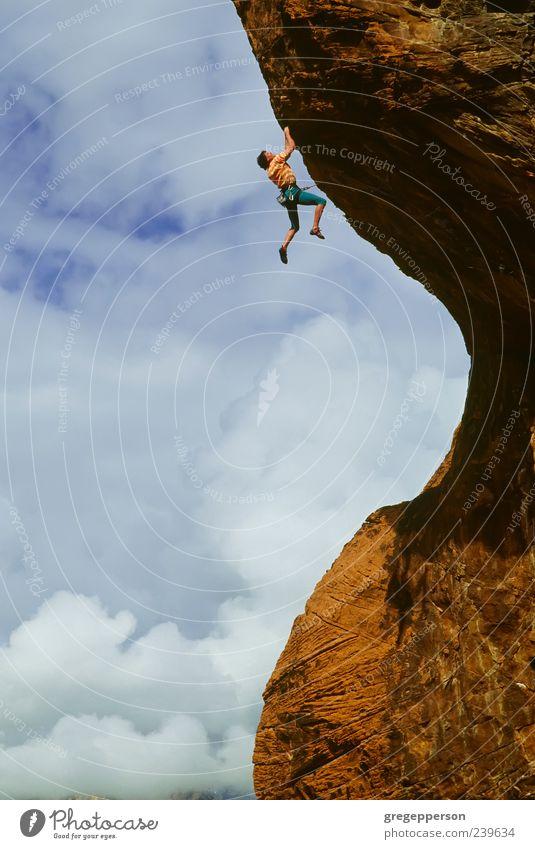 Kletterer, der sich an eine Klippe klammert. Abenteuer Sport Klettern Bergsteigen Erfolg Junger Mann Jugendliche 1 Mensch 18-30 Jahre Erwachsene Unwetter Felsen