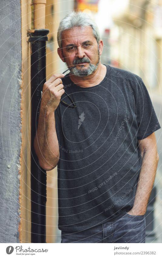 Erwachsener Mann, der vor der Kamera im urbanen Hintergrund steht. Lifestyle Glück Mensch maskulin Männlicher Senior 1 45-60 Jahre 60 und älter Straße