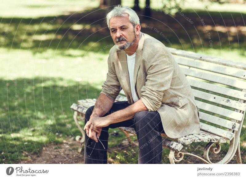 Nachdenklicher reifer Mann, der auf einer Bank in einem Stadtpark sitzt. Lifestyle Glück Ruhestand Mensch maskulin Erwachsene Männlicher Senior 1 45-60 Jahre