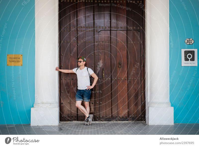 junger Mann wartet an einer Holztür und stützt sich ab Kuba Havanna Insel Ferien & Urlaub & Reisen Reisefotografie Ausflug Sightseeing Straße Stadt blau Fernweh