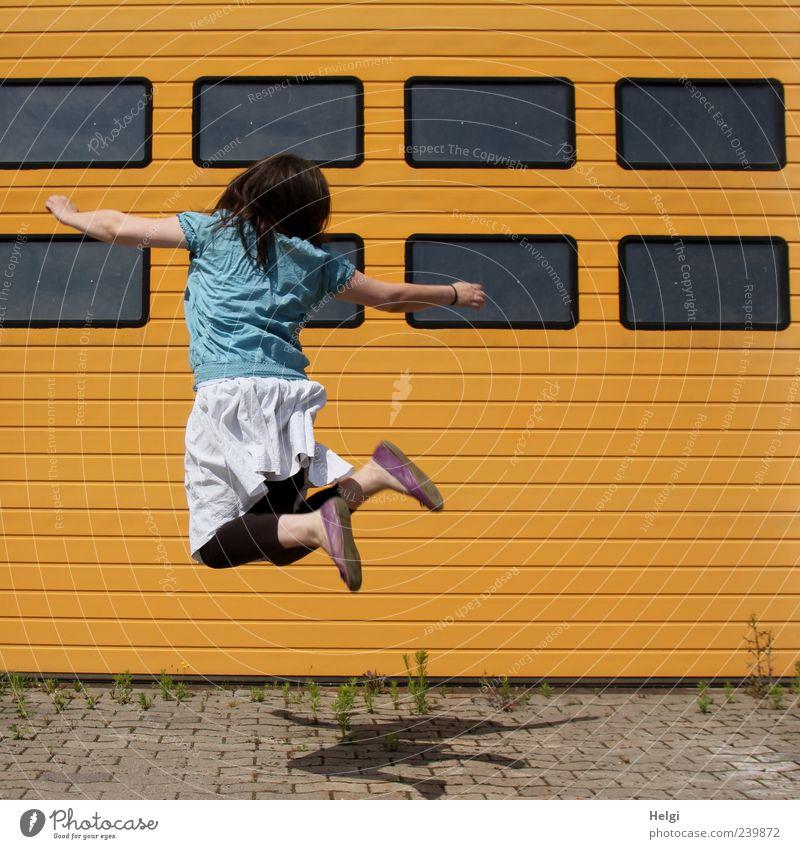 Rückansicht einer Fau, die vor einem Rolltor in die Höhe springt Freizeit & Hobby Mensch Junge Frau Jugendliche Erwachsene Leben 1 Industrieanlage Gebäude