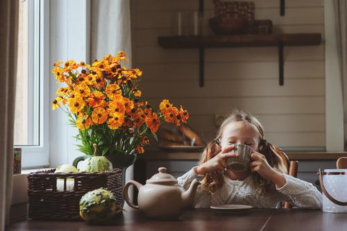 Kind Mädchen beim Frühstück zu Hause Tee Lifestyle Glück Dekoration & Verzierung Stuhl Tisch Küche Familie & Verwandtschaft Herbst Wärme Blume sitzen modern