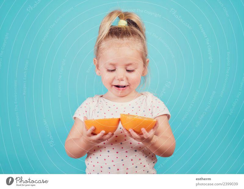 lächelndes Baby mit einer Orange auf blauem Hintergrund Lebensmittel Frucht Ernährung Essen Lifestyle Freude Wellness Mensch feminin Mädchen Kindheit 1