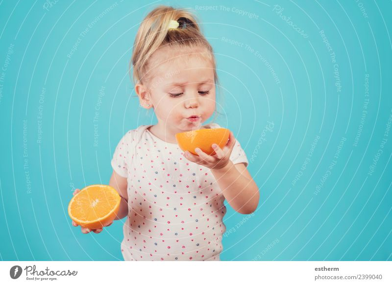 Baby isst eine Orange auf blauem Hintergrund Lebensmittel Frucht Ernährung Essen Frühstück Mittagessen Mensch feminin Mädchen Kindheit 1 3-8 Jahre Diät