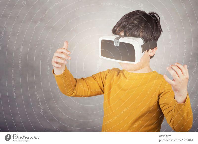 Junge spielt mit einer Virtual-Reality-Brille auf grauem Hintergrund Lifestyle Freude Spielen Hardware Technik & Technologie Unterhaltungselektronik