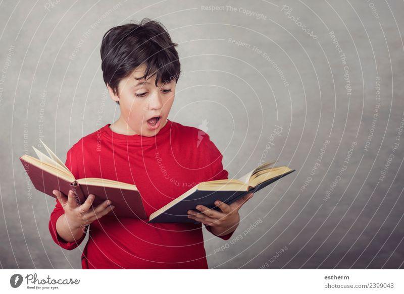 Junge liest Bücher auf grauem Hintergrund Lifestyle Freude lesen Bildung lernen Schulkind Prüfung & Examen Mensch maskulin Kind Kindheit 1 8-13 Jahre festhalten
