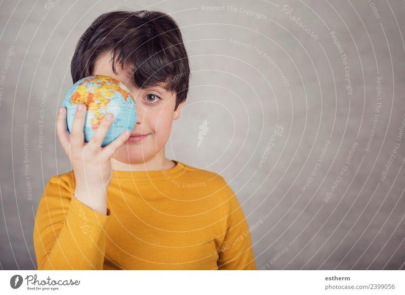 lächelnder Junge mit einer Erdkugel, die sein Auge bedeckt. Freude Ferien & Urlaub & Reisen Tourismus Ausflug Abenteuer Mensch maskulin Kind Kleinkind Kindheit