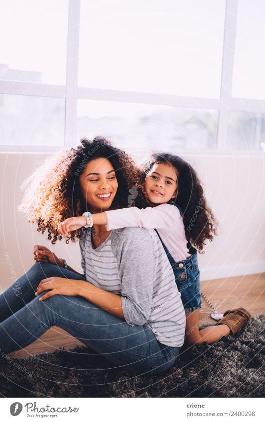 afrikanische Tochter, die ihre Mutter zu Hause umarmt. Glück schön Leben Kind Frau Erwachsene Eltern Familie & Verwandtschaft Kindheit Lächeln Liebe Umarmen