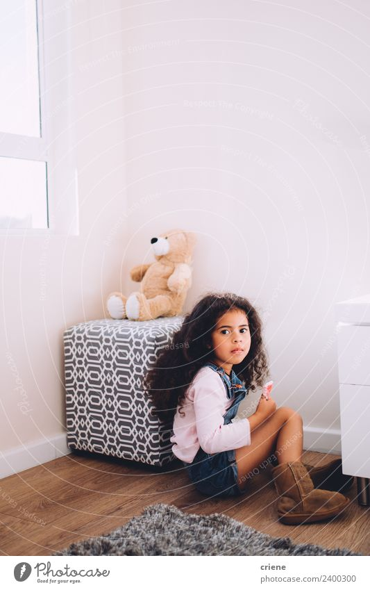 Afrikanisches Mädchen sitzt neben ihrem Teddybären zu Hause. Glück schön Kind Stiefel Spielzeug sitzen klein niedlich Bär heimwärts Raum Hintergrund Fenster