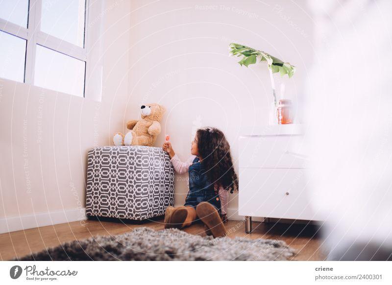 Afrikanisches Mädchen gibt Teddybonbons zu Hause. Glück schön Spielen Kind Stiefel Spielzeug Teddybär sitzen klein niedlich Bär heimwärts Raum Hintergrund