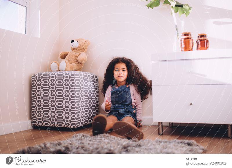 kleines afrikanisches Mädchen hält einen Lutscher, der auf dem Boden sitzt. Glück schön Kind Pflanze Stiefel Spielzeug Teddybär Lächeln sitzen niedlich Bär