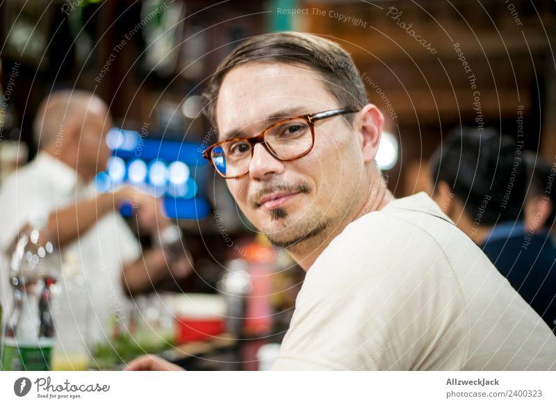 Portrait junger mann mit Brille an einer Bar Kuba Havanna Junger Mann Brillenträger Blick in die Kamera Zufriedenheit Lächeln Porträt Bart sitzen warten