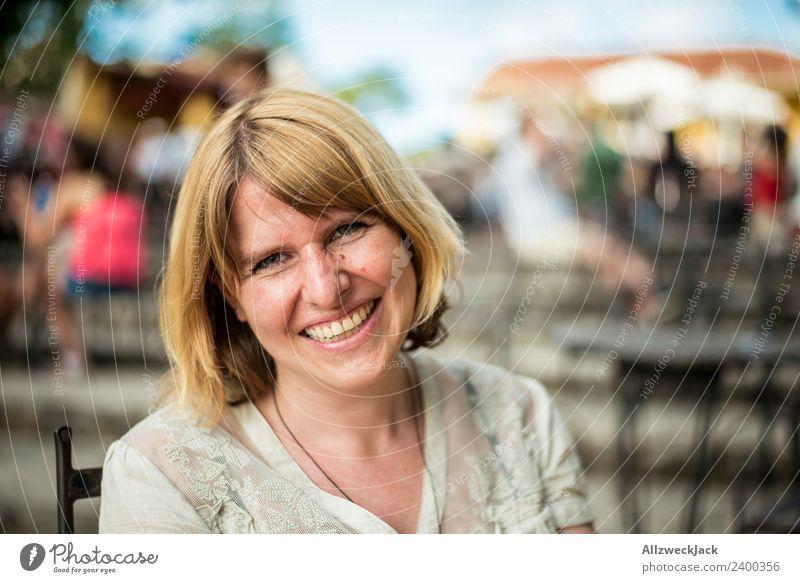 Portrait von einer glücklichen jungen Frau lachend Tag Außenaufnahme Porträt 1 Mensch Junge Frau blond mittellang schulterlang Blick nach vorn positiv