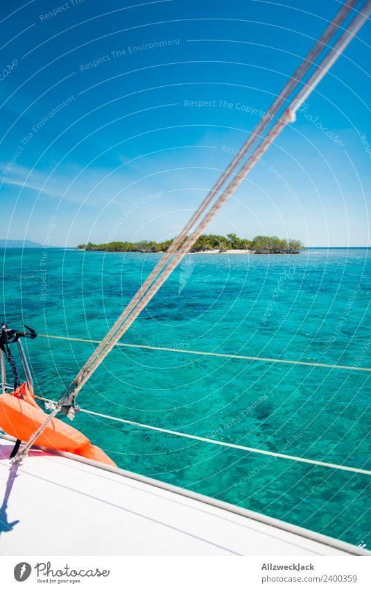 Blick vom Boot auf eine kleine Insel in der Karibik Tag Menschenleer Paradies Klarheit traumhaft Wasser Meer Segeln Segelboot maritim Blauer Himmel