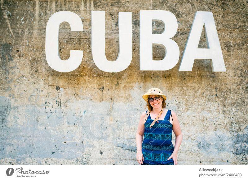 Frau mit blauem Kleid und Hut vor dem Wort CUBA Ferien & Urlaub & Reisen Junge Frau Freude Reisefotografie Wand feminin Mauer Zufriedenheit Schriftzeichen