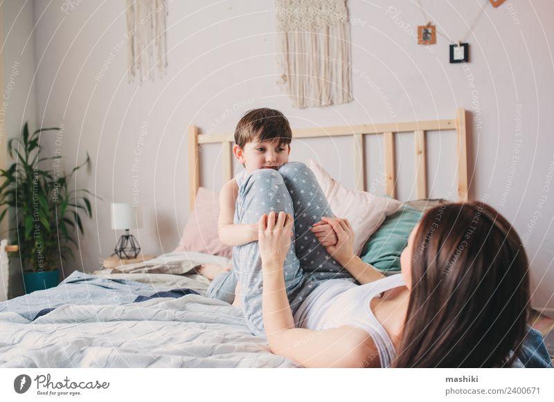 glückliche Mutter und Kind Sohn spielen im Bett Lifestyle Freude Glück Leben Erholung Spielen Schlafzimmer Kleinkind Junge Eltern Erwachsene