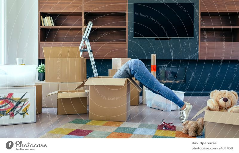 Frau in einer Box, die den Umzug vorbereitet. Lifestyle Haus Umzug (Wohnungswechsel) Wohnzimmer Mensch Erwachsene Jeanshose Turnschuh Spielzeug Teddybär