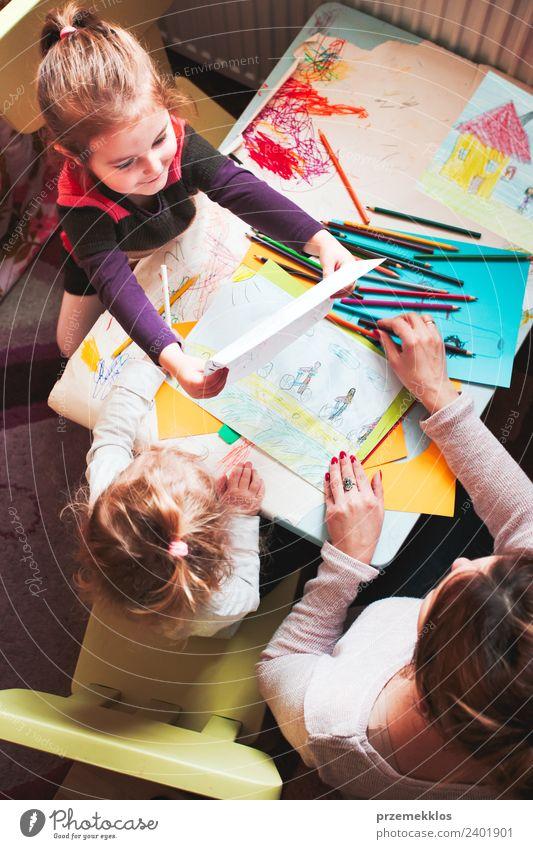 Kleines Mädchen zeigt ihr Bild von ihrer Mutter. Lifestyle Freude Glück Tisch Kindererziehung Bildung Kindergarten Schule Handwerk Mensch Frau Erwachsene Eltern
