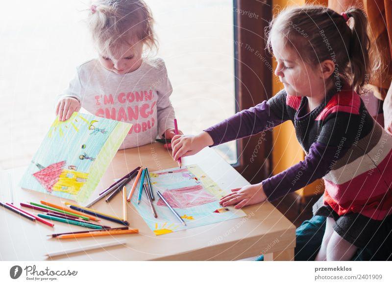 Zwei kleine Mädchen, die die bunten Bilder zeichnen. Lifestyle Freude Glück Handarbeit Tisch Bildung Kindergarten Schule Handwerk Mensch Schwester