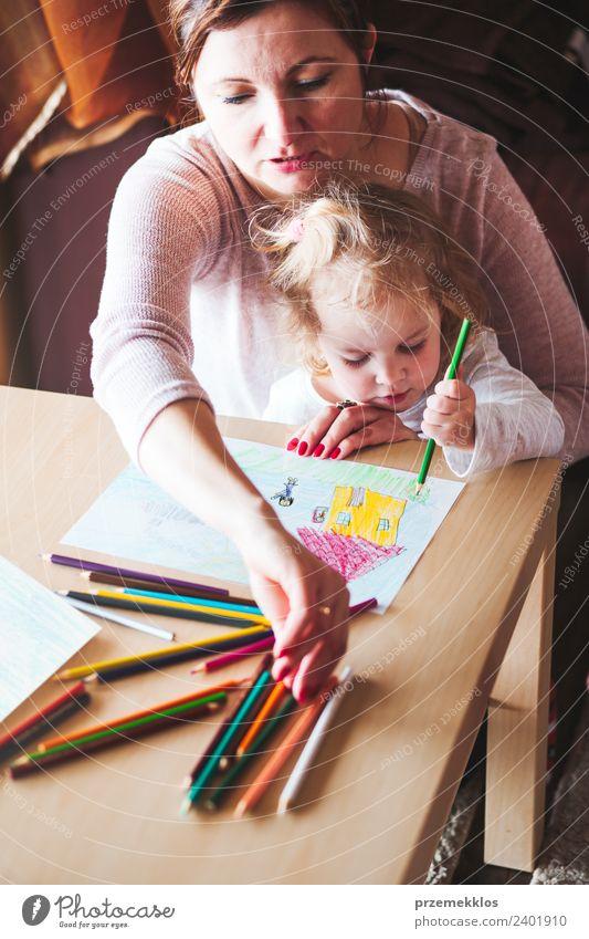 Mama mit kleiner Tochter, die die bunten Bilder zeichnet. Lifestyle Freude Glück Handarbeit Tisch Kindergarten Schule Mensch Mädchen Frau Erwachsene Eltern