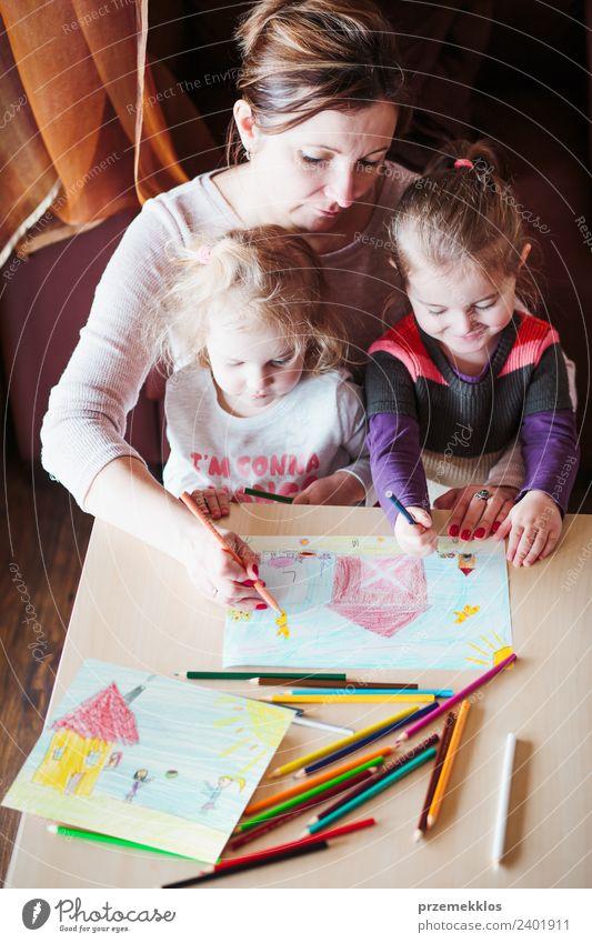 Mama mit kleinen Mädchen, die ein buntes Bild zeichnen. Lifestyle Freude Glück Handarbeit Tisch Kindererziehung Bildung Kindergarten Schule Mensch Eltern