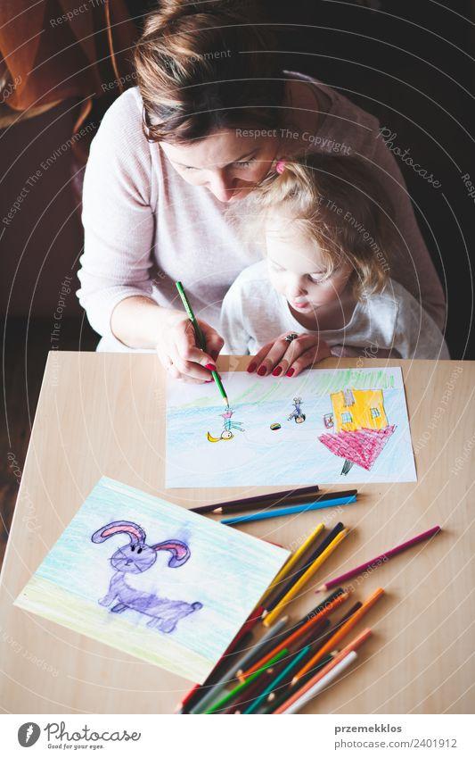 Mama mit kleiner Tochter, die ein buntes Bild zeichnet. Lifestyle Freude Glück Handarbeit Tisch Kindererziehung Bildung Kindergarten Schule Handwerk Mensch