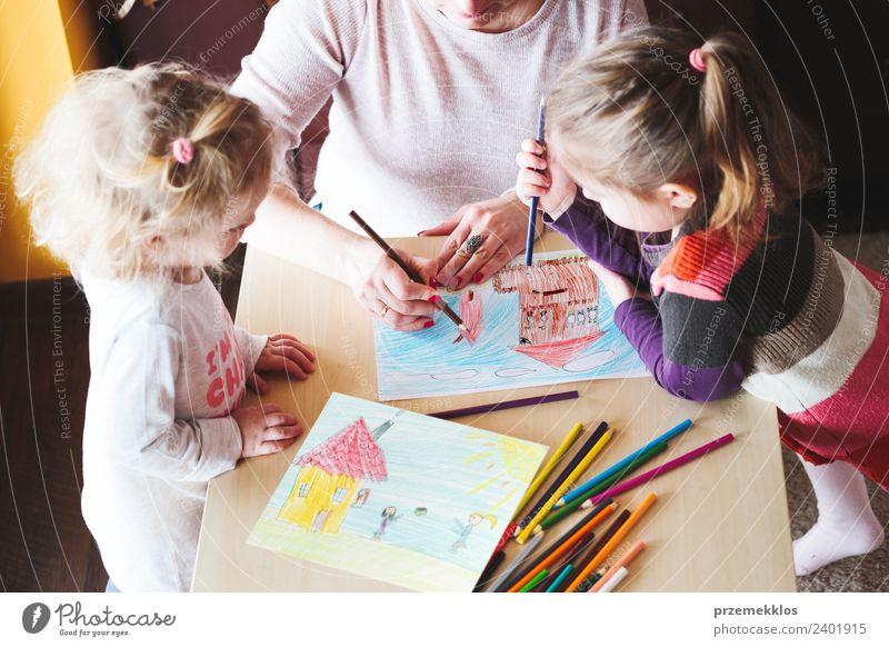 Mutter mit kleinen Mädchen, die ein buntes Bild von Haus und spielenden Kindern mit Bleistiftmalen malen, die drinnen am Tisch stehen Lifestyle Freude Glück