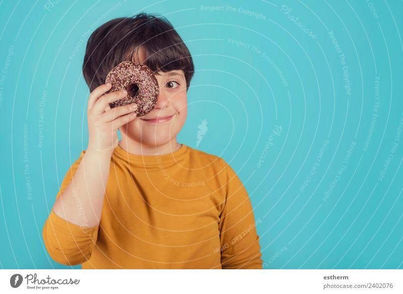 lächelnder Junge hält Donuts über ihr Auge. Lebensmittel Brötchen Süßwaren Schokolade Ernährung Lifestyle Freude Mensch maskulin Kind Kleinkind Kindheit 1