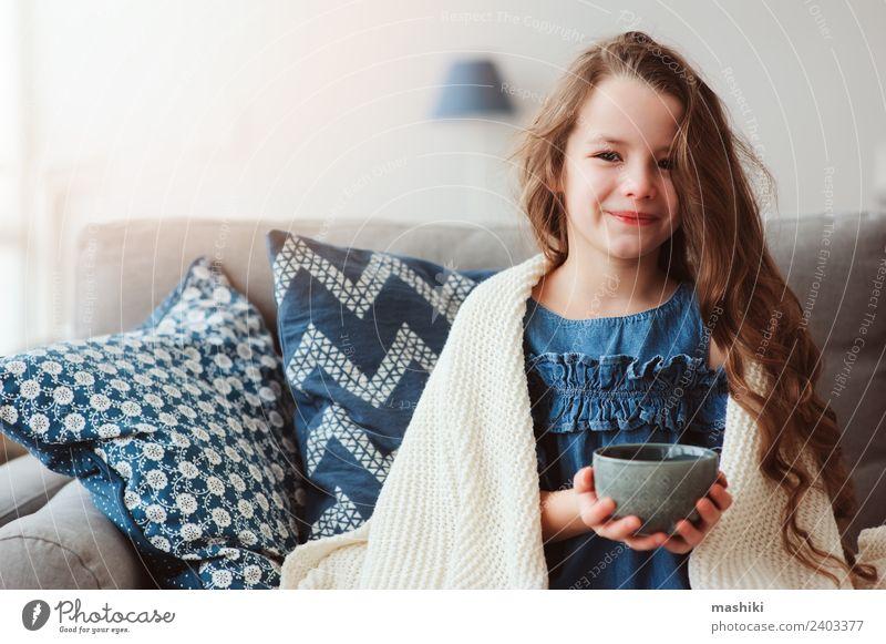 Kind Mädchen trinkt heißen Tee, um sich von der Grippe zu erholen. Krankheit Erholung Winter Wohnzimmer Wärme genießen Lächeln sitzen klein modern natürlich