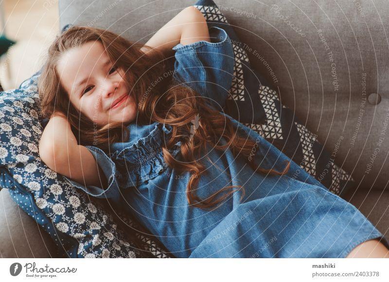 süßes glückliches 5 Jahre altes Kind Mädchen Lifestyle Freude Glück Erholung Wohnzimmer Frau Erwachsene Kindheit Mode Kleid Lächeln sitzen träumen Coolness