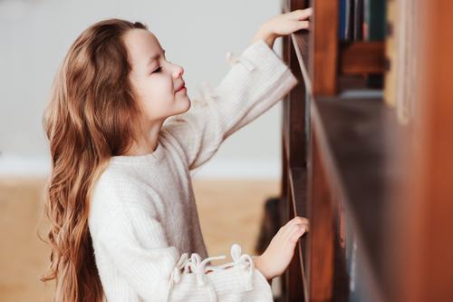 glücklich smart Schulmädchen lesen Bücher Kind Schule Klassenraum Schulkind Kindheit Buch Bibliothek klein klug Konzentration Kreativität lernen Mädchen Bildung