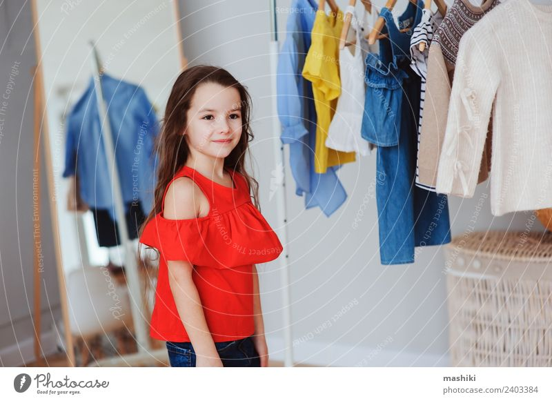 süßes kleines Kind Mädchen bei der Auswahl neuer Kleidung kaufen Stil Mode Bekleidung Sammlung Lächeln hell trendy modern rot Farbe Outfit viele wählen anhaben