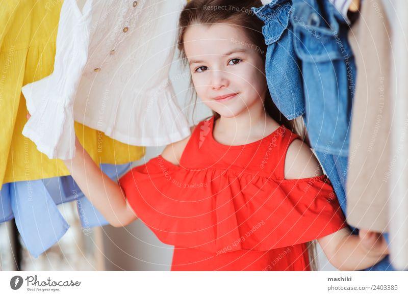 süßes kleines Kind Mädchen bei der Auswahl neuer Kleidung kaufen Stil Mode Bekleidung Sammlung Lächeln hell trendy modern Farbe Outfit viele