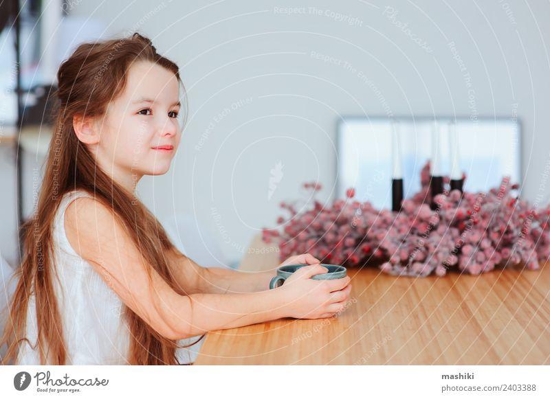glückliches 5 Jahre altes Kind Mädchen beim Frühstück zu Hause Ernährung Kakao Tee Lifestyle Glück Tisch Küche Kindheit Lächeln sitzen authentisch heiß modern