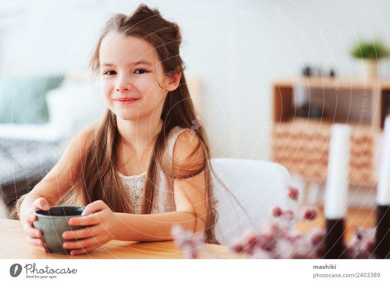 glückliches 5 Jahre altes Kind Mädchen beim Frühstücken Ernährung Kakao Tee Lifestyle Glück Tisch Küche Kindheit Lächeln sitzen authentisch heiß modern