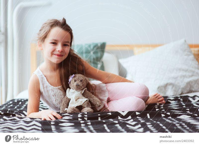 süßes glückliches Kind Mädchen entspannend zu Hause auf dem Bett Lifestyle Freude Erholung Spielzeug Teddybär Lächeln schlafen träumen klein lustig niedlich