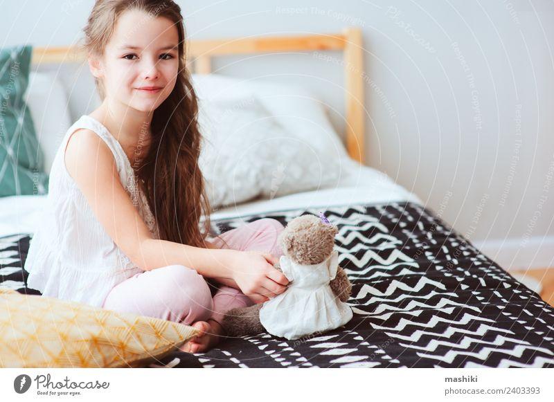 süßes glückliches Kind Mädchen entspannend zu Hause auf dem Bett Lifestyle Freude Erholung Schlafzimmer Spielzeug Teddybär Lächeln schlafen träumen klein lustig