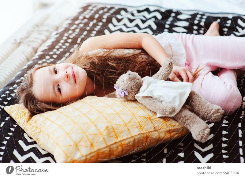 süßes glückliches Kind Mädchen entspannend zu Hause Lifestyle Freude Erholung Schlafzimmer Lächeln schlafen träumen klein lustig Energie Bett aufwachen
