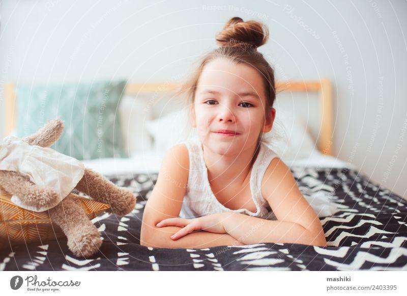 fröhliches kleines Kind Mädchen, das morgens auf ihrem Bett liegt. Lifestyle Freude Glück Haare & Frisuren Erholung Sonne Schlafzimmer Spielzeug Teddybär