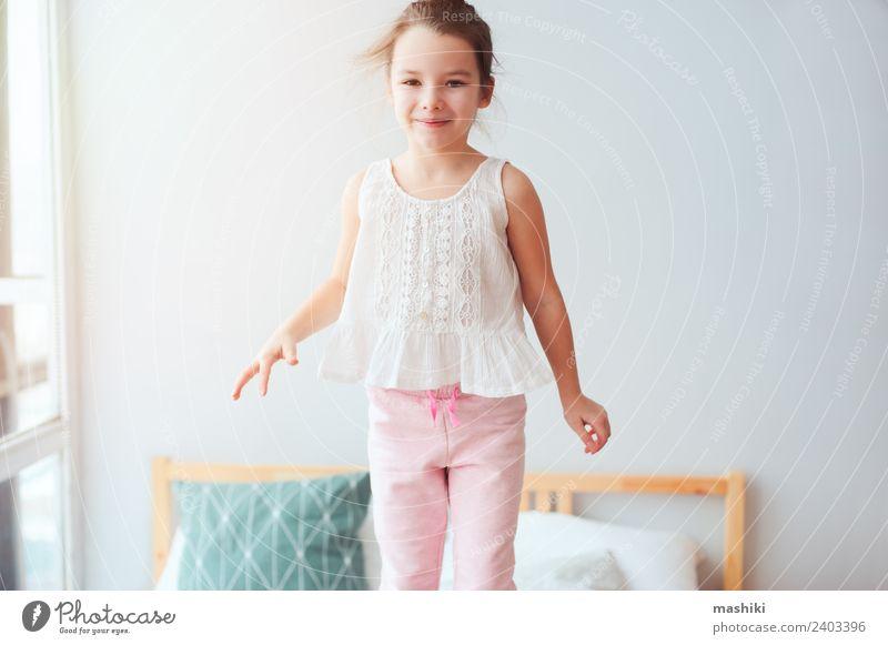 glückliches Kind Mädchen springt auf Bett Lifestyle Freude Glück Haare & Frisuren Erholung Sonne Schlafzimmer Spielzeug Teddybär Lächeln schlafen träumen klein