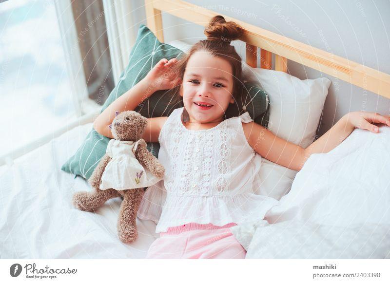 glückliches Kind Mädchen erwacht am frühen Morgen Lifestyle Freude Glück Haare & Frisuren Erholung Sonne Schlafzimmer Spielzeug Teddybär Lächeln schlafen
