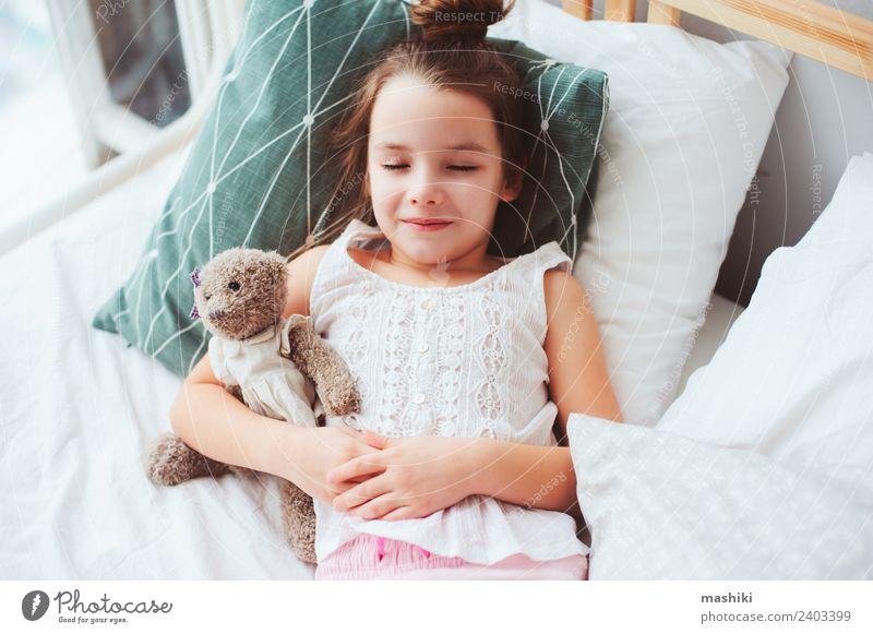 süßes kleines Kind Mädchen schläft in einem bequemen Bett. Lifestyle Freude Erholung Schlafzimmer Spielzeug Teddybär Lächeln schlafen träumen lustig niedlich