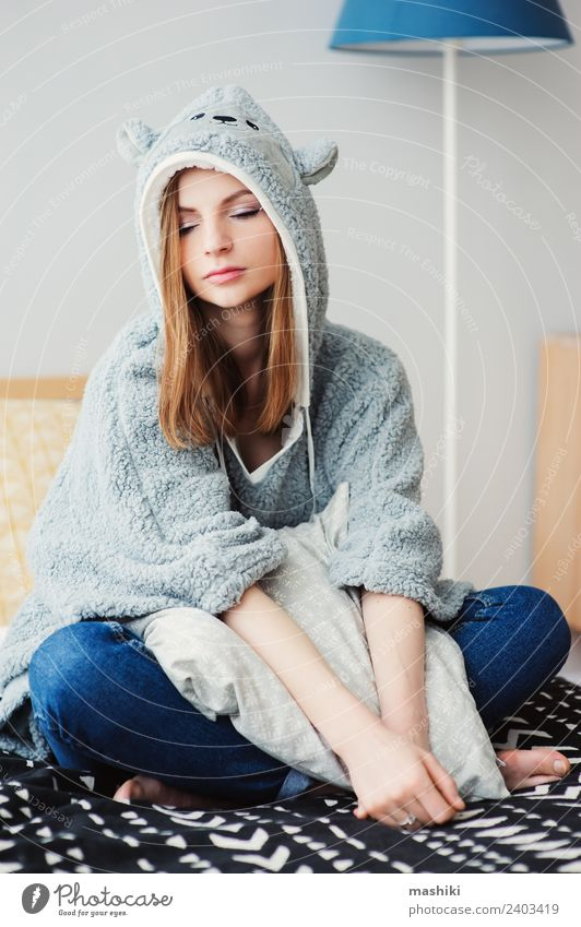 junge schöne Frau, die sich zu Hause entspannt. Lifestyle Leben Erholung Schlafzimmer Erwachsene Kultur Wärme Mode sitzen träumen modern natürlich grau