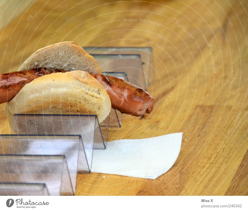 Snack Lebensmittel Wurstwaren Brötchen Ernährung frisch heiß lecker Appetit & Hunger Imbiss Serviette Holztisch Farbfoto Nahaufnahme Textfreiraum rechts