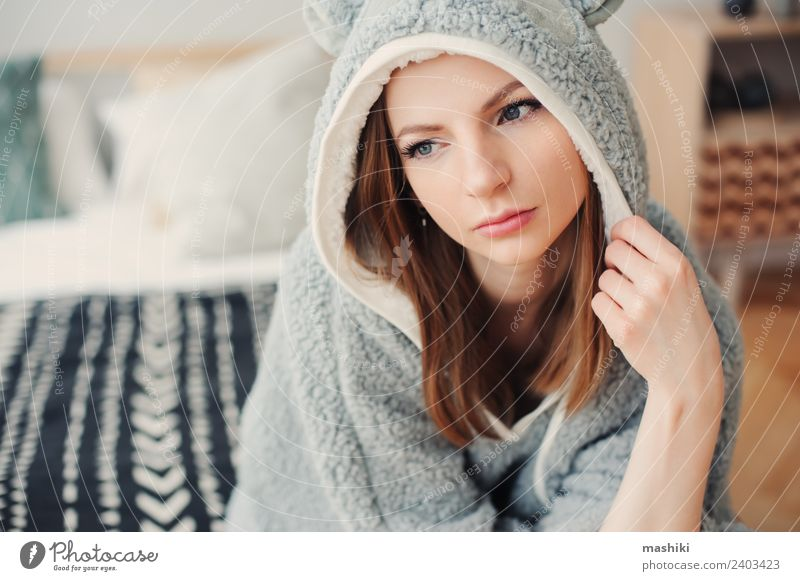 junge schöne Frau, die sich zu Hause entspannt. Lifestyle Leben Erholung Schlafzimmer Erwachsene Kultur Wärme Mode sitzen träumen lustig modern natürlich grau