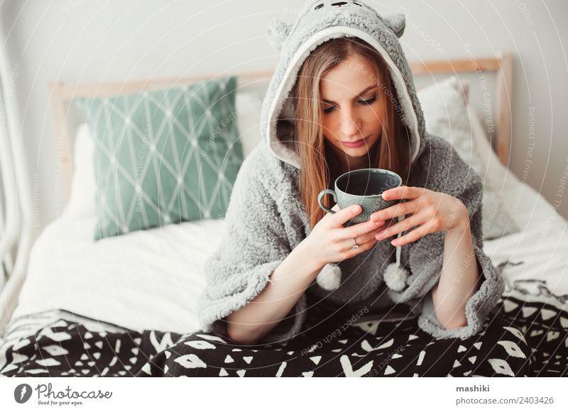 junge schöne Frau, die sich zu Hause entspannt. Kaffee Tee Lifestyle Leben Erholung Schlafzimmer Erwachsene Kultur Wärme Mode sitzen träumen lustig modern