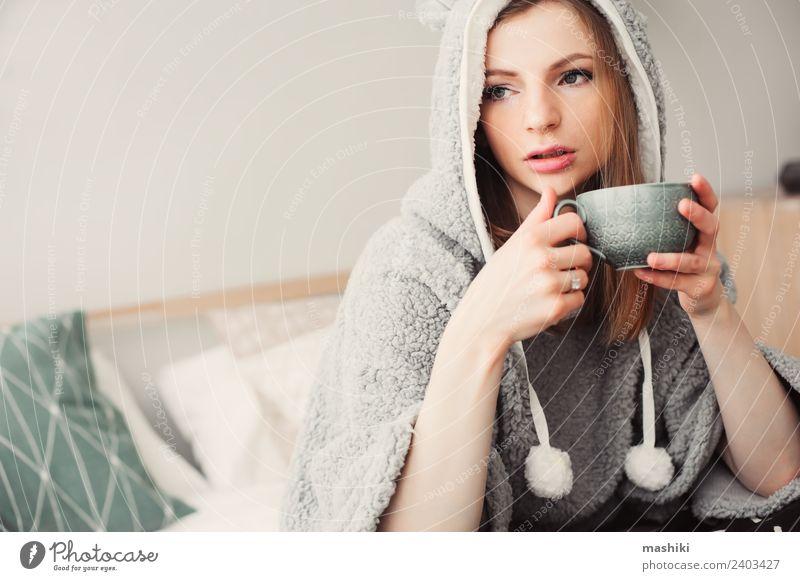 junge schöne Frau, die sich zu Hause entspannt. Kaffee Tee Lifestyle Leben Erholung Schlafzimmer Erwachsene Kultur Wärme Mode sitzen träumen modern natürlich