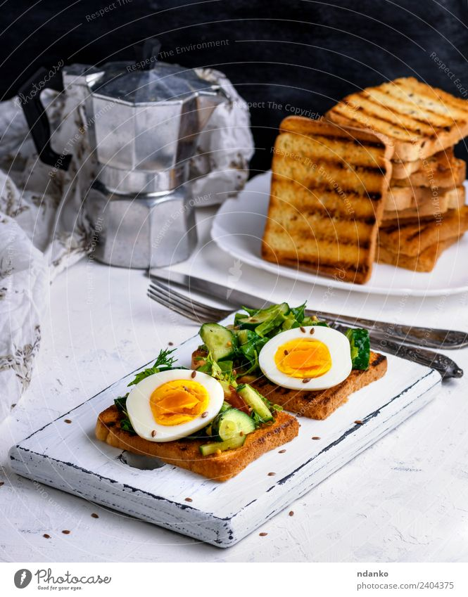 Brot aus Weizenweißmehl mit gekochtem Ei Gemüse Frühstück Mittagessen Abendessen Vegetarische Ernährung Kaffee Teller Gabel Essen frisch lecker braun grün